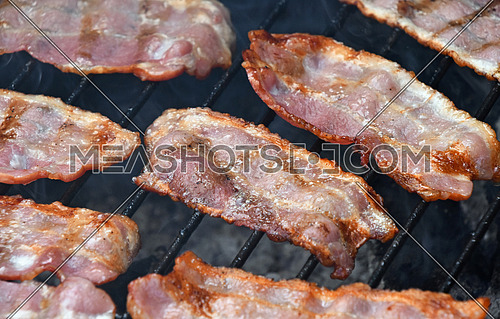 Crispy smoked grilled barbecue bacon slices, cooked on bbq smoke grill, close up