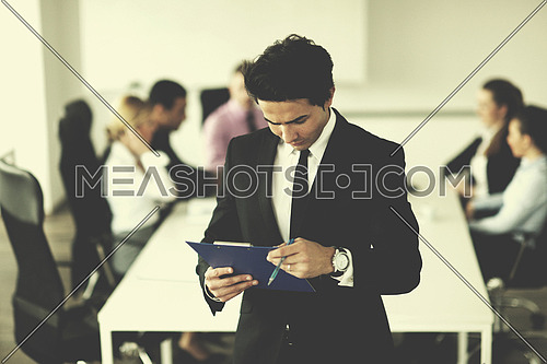 Confident young business man attending a meeting with his colleagues