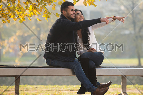 Young Couple Searching Goal In The Distance While Sitting On A Bench