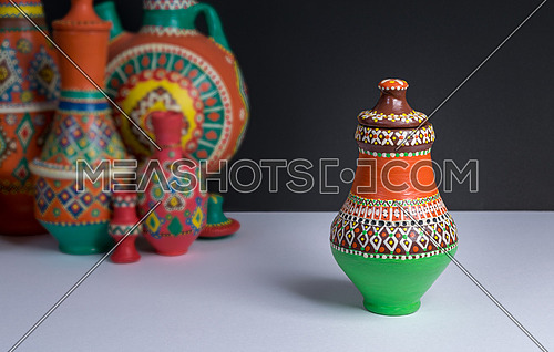 Still life of one ornate colorful pottery vase on background of blurred group of colorful vases, white table and black wall