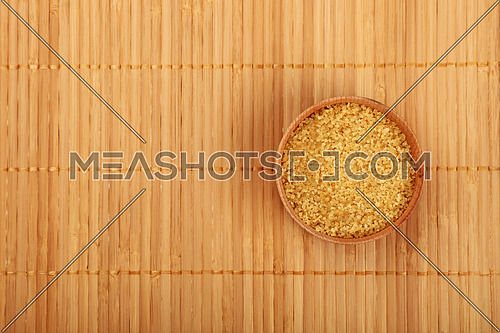 Small wooden round full bowl of brown cane sugar on bamboo mat background, top view