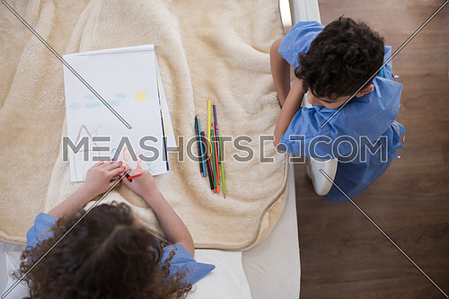 top view of little middle eastern girl painting home and family at hospital bed