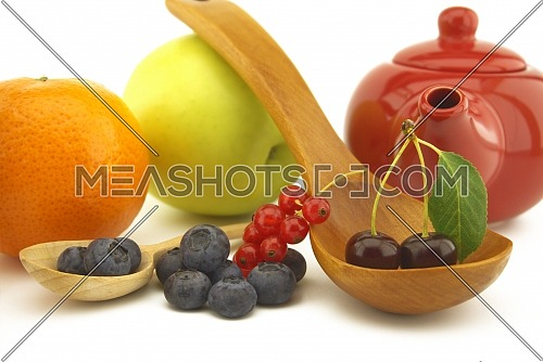 Fresh seasonal fruit still life with assorted berries including blueberries, cherries and red currants on wooden spoons with apple and orange and colorful red teapot
