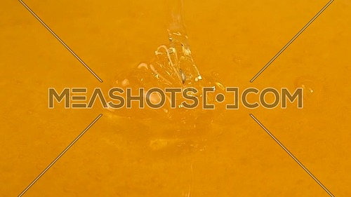 Close up fresh thick fluid acacia honey pouring and flowing to bowl, high angle view, slow motion
