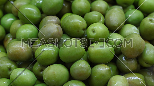 Green whole castelvetrano olives close up background, retail market stall display