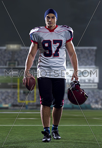 portrait of young confident American football player walking through the big modern american football stadium with lights and flares at night