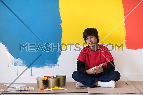 young boy painter resting after painting the wall, sitting on the floor in new home