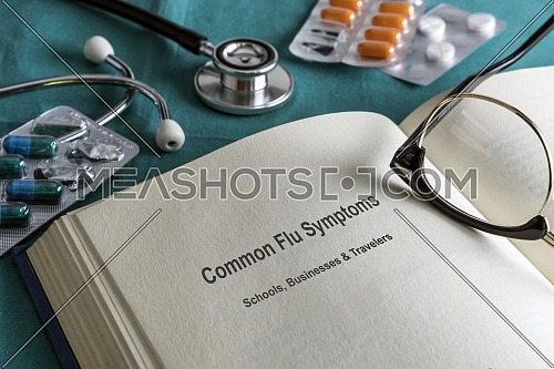Book page medicine of common flu symptoms in schools, businesses and travelers, current metaphorical image, horizontal composition