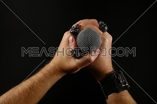 Close up man two hands with metal rings and bracelet holding microphone over black background, side view