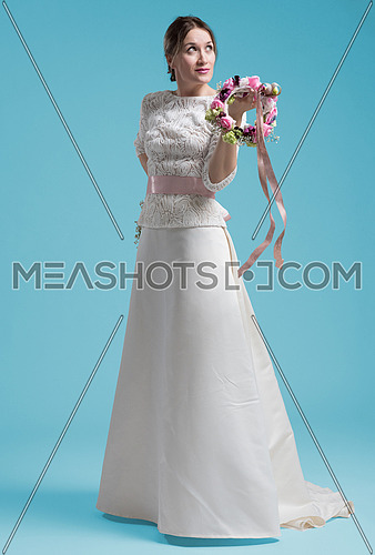 portrait of beautiful young woman as bride in wedding dress isolated on cyan backgrond in studio