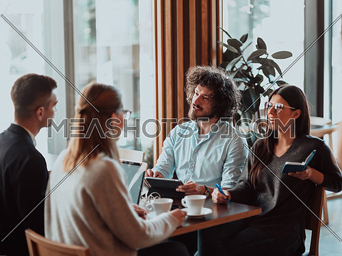 a group of young entrepreneurs on a coffee break discuss the project while using modern editing tablets, a smartphone and a laptop
