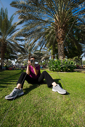 A woman sitting on the grass holding a camera in a park
