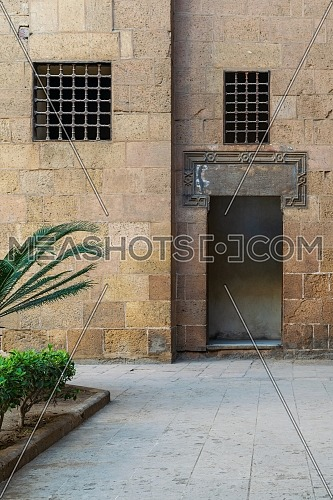 Ancient external old decorated bricks stone wall with two windows and opened door leading to Ottoman era Beit El Sehemy historical building, Cairo, Egypt