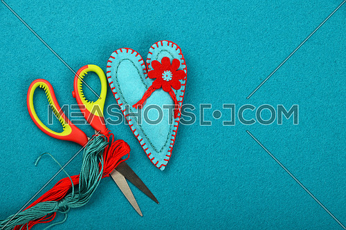 Craft and art, one blue handmade stitched toy heart, red thread and scissors on teal background