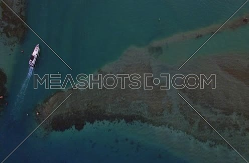 Drone shot flying above the red sea and a yacht moving at Day