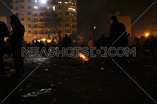 a wide shot for tahrir square at night during revolution and fire on the ground
