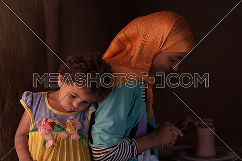Young girl at pottery school with her you sister attached to her in Tunis Village, Fayoum, Egypt