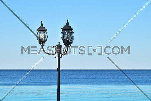 Old vintage black metal street lantern lamppost over blue seascape and clear sky