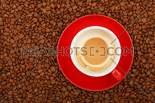 Full latte cappuccino with milk in big red cup with saucer on background of roasted coffee beans, elevated top view, close up