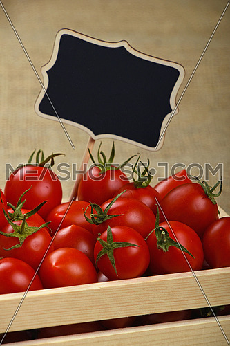 Fresh red ripe cherry tomatoes in small wooden box with black chalkboard price sign tag over jute burlap canvas background