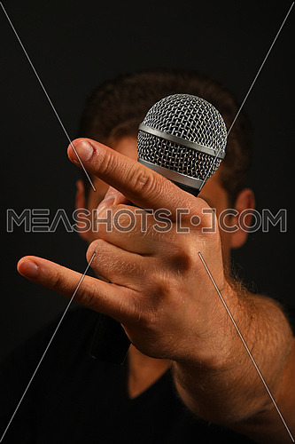 Male hand holding microphone with devil horns rock metal sign with head behind isolated on black background