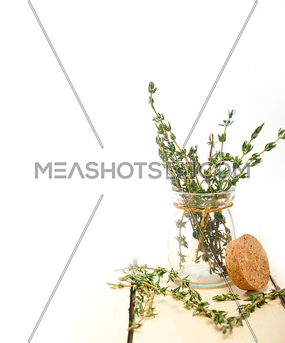 fresh thyme on a glass jar over a white wood rustic table