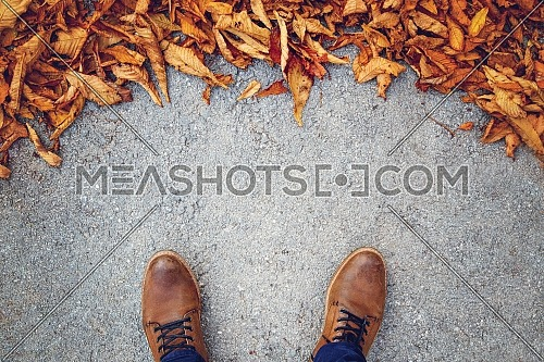 Top shot for Leaves has fallen on the concrete ground. Male shoes on street with leaves.