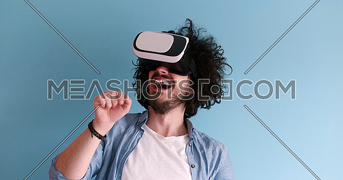 Happy man getting experience using VR headset glasses of virtual reality, isolated on blue background