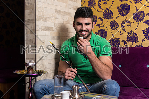 Man Smoking Turkish Hookah In The Cafe With Colorful Walls On Background