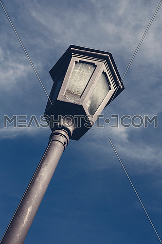 Street lamp and clouds against blue sky