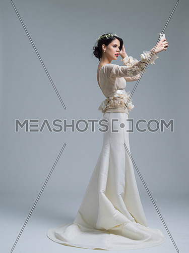 beautiful bride taking a selfie with her cell phone isolated on white background