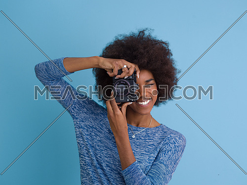 portrait of a smiling pretty african american girl taking photo on a retro camera isolated over blue background