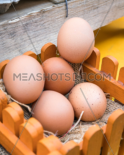 Brown chicken eggs leaning on straw in wooden basket.