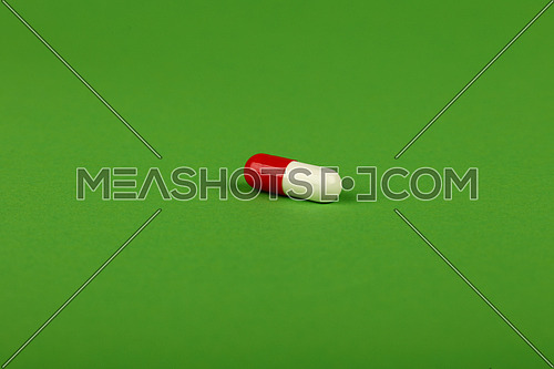 Close up one red and white gel cap pill of medicine over natural green background with copy space, high angle view