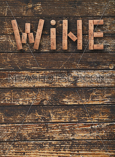 Word WINE shaped by natural wooden wine bottle corks of different vintage years over background of dark old wooden planks