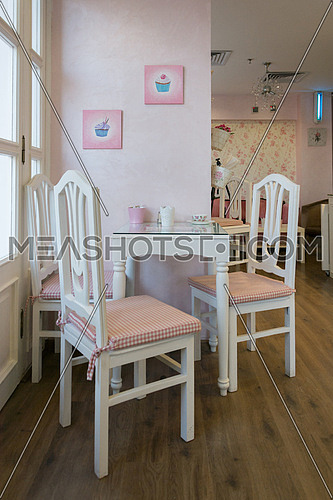 a white dining table with three chairs