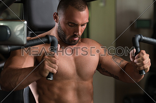 Big Man In The Gym Is Exercising Back On Machine - Muscular Athletic Bodybuilder Model Exercise In Fitness Center