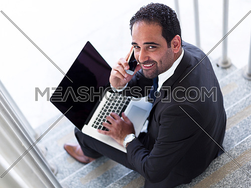handsome young middle eastern business man working on laptop computer online while sitting on steps in front of modern corporate office building and speaking by phone