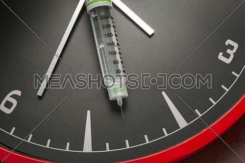 medicine vials and syringe, the clock shows the time of the medication