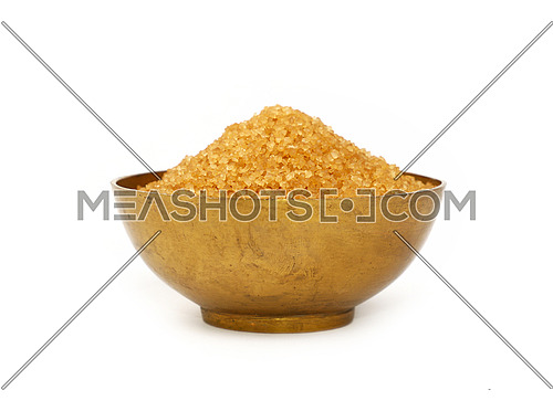 Close up one vintage bronze metal bowl full of raw brown cane sugar, isolated on white background, low angle side view