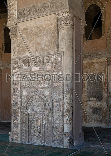 Ornate engraved stone wall with floral patterns and calligraphy in front of the foundation stone of Ahmed Ibn Tulun Mosque with engraved formation text, Cairo, Egypt