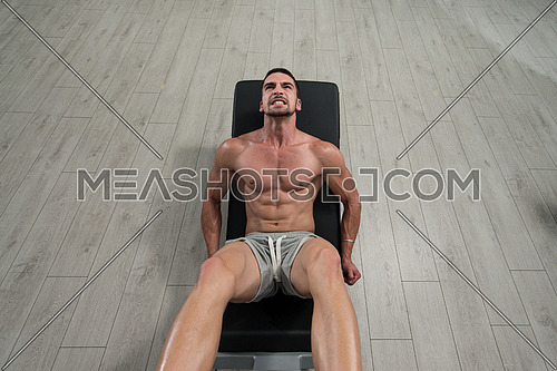 Young Man Using The Leg Press Machine At A Health Club In Gym
