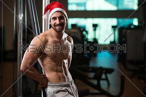 Portrait Of A Young Santa Claus Posing And Showing Bodybuilding Pose In Gym