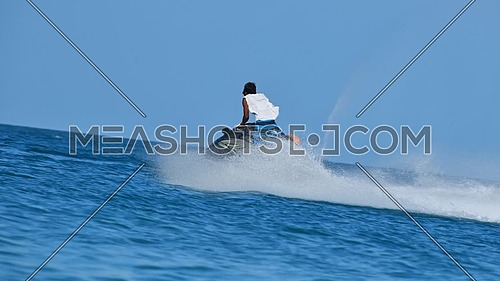 Cinemagraph of one young man riding jet ski scooter over blue sea water with splash trace behind, low angle view