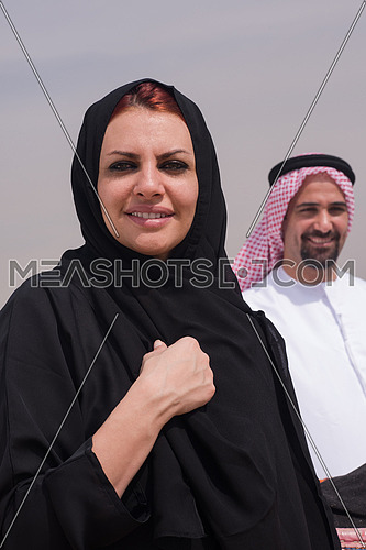 portrait of  Emiratie young  man and his wife as tourists at the pyramids