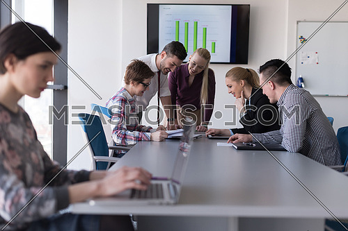 young  business woman at modern startup office interior working on laptop computer, blured team in meeting, people group in background
