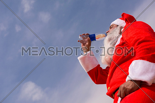 santa claus drinking water in the desert heat