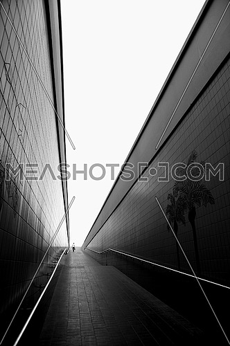 A pedestrian tunnel with a man at the far end in black and white