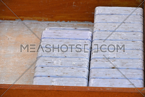 Close up blue lavender traditional beauty toilet hard soap bars in wooden box on retail display, high angle view
