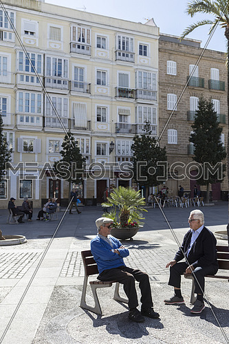 Elderly talk sitting on a bench with tranquility in a beautiful square of Cadiz, Andalusia, Spain